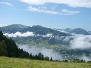 mráčky okolo vrcholu Hahnenkamm a města Kitzbühl
